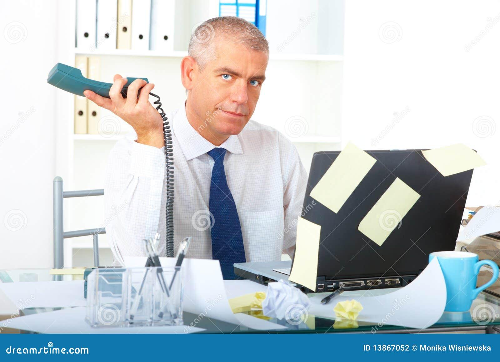 Hombre de negocios tensionado que se sienta en el escritorio