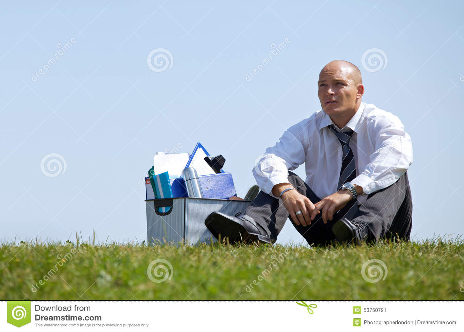 Hombre de negocios triste que se sienta al lado de cesta por completo de ficheros en parque
