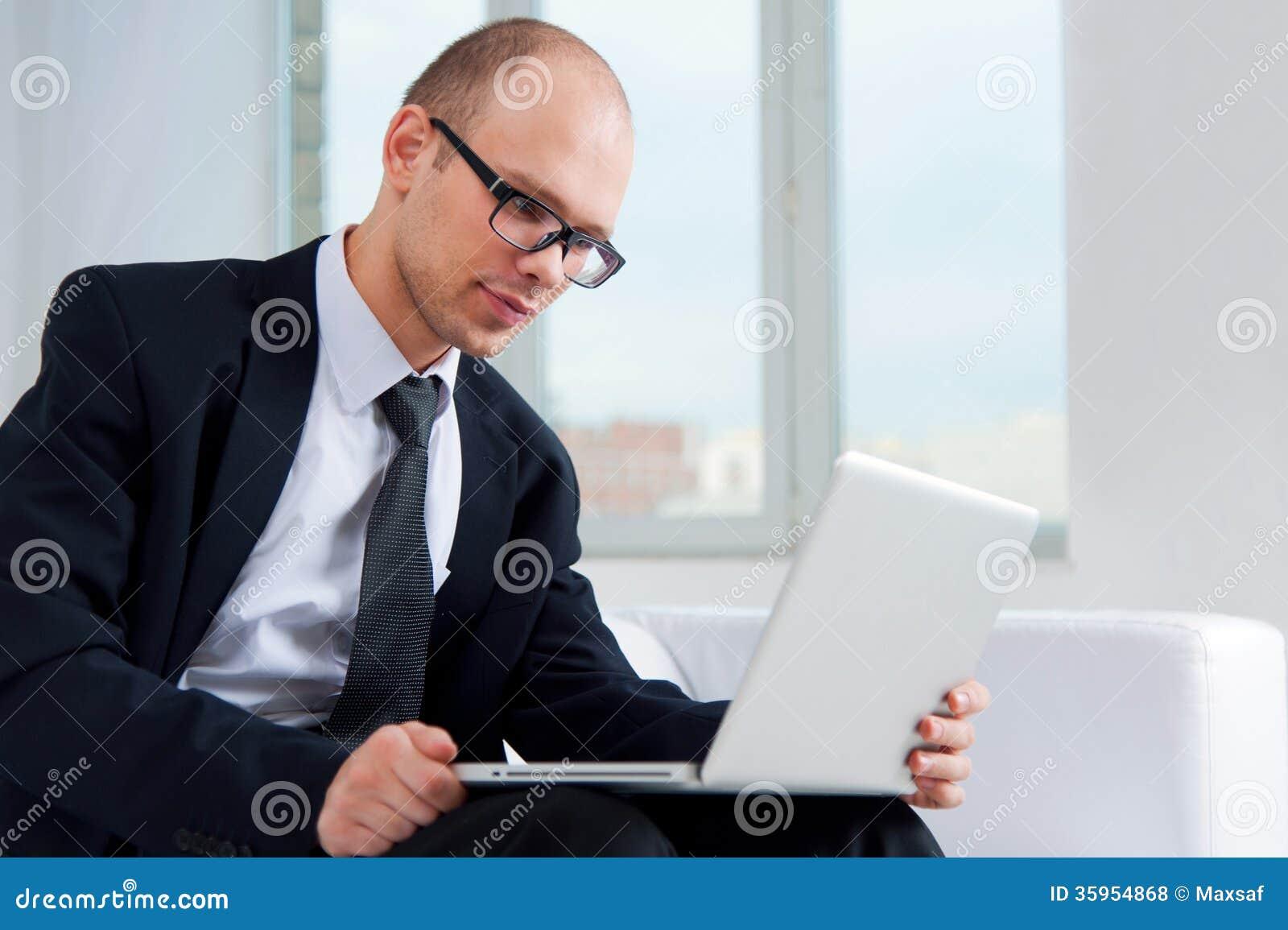 Hombre de negocios usando el ordenador portátil en el sofá