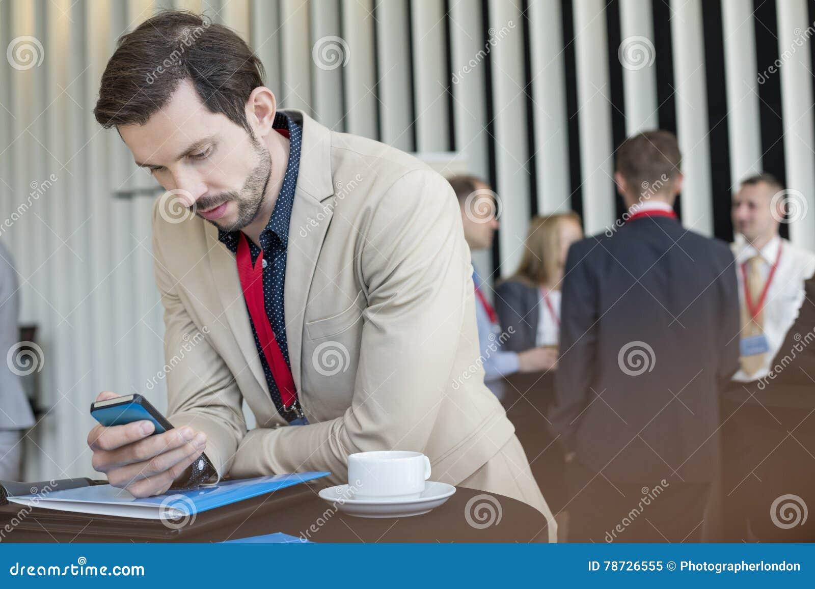 Hombre de negocios usando el teléfono elegante mientras que descanso para tomar café en centro de convenio