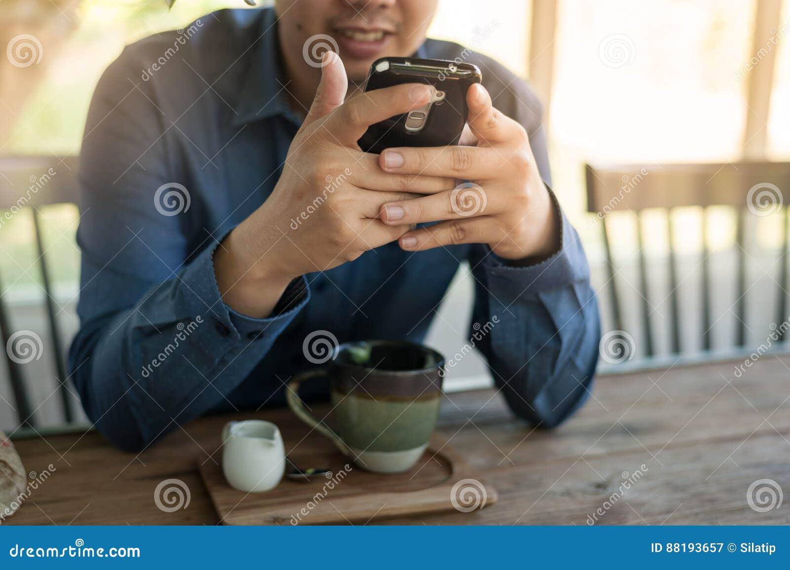 Hombre de negocios usando el teléfono móvil mientras que se sienta en cafetería