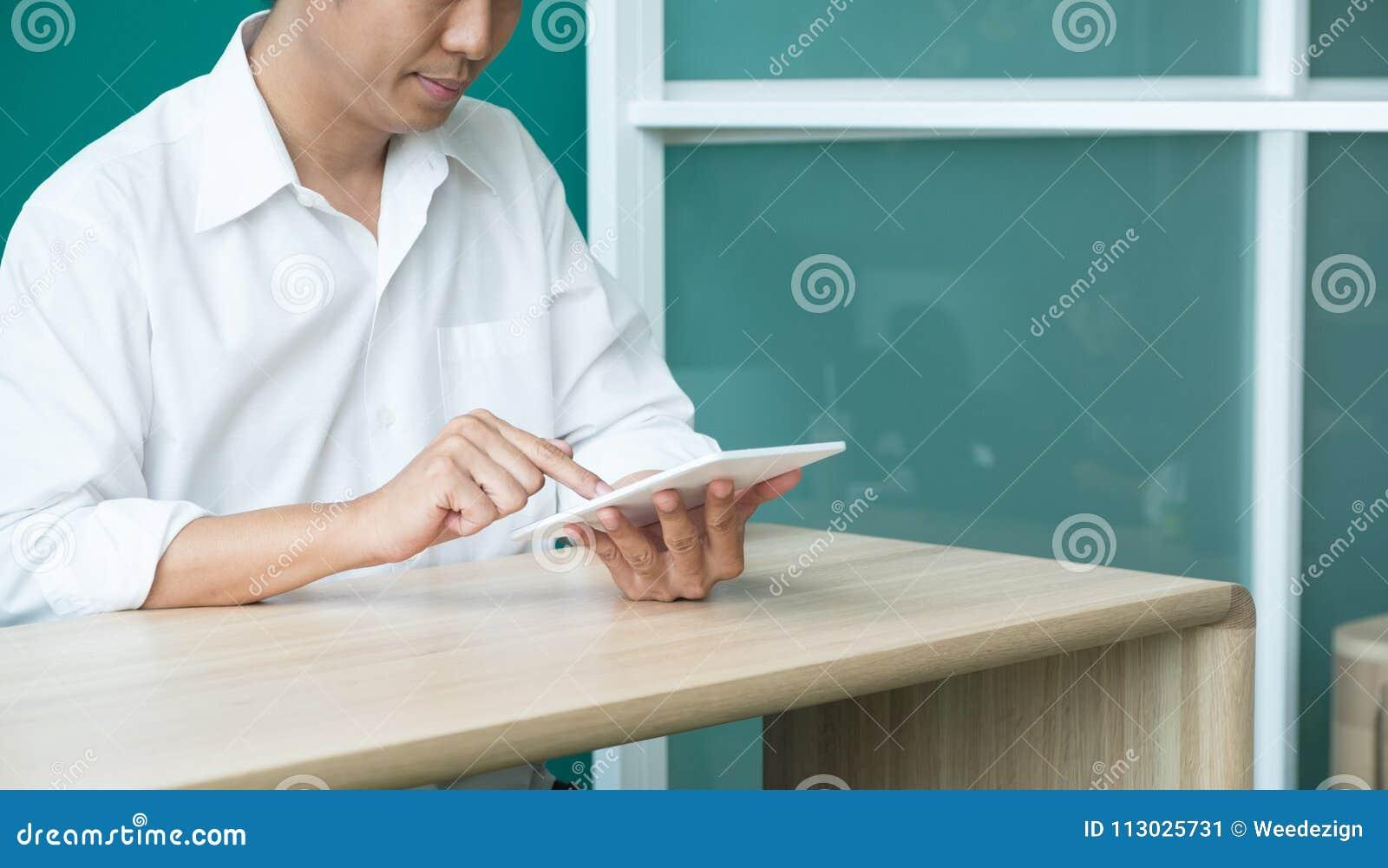 Hombre de negocios usando la tableta en el escritorio en la oficina, después del workin