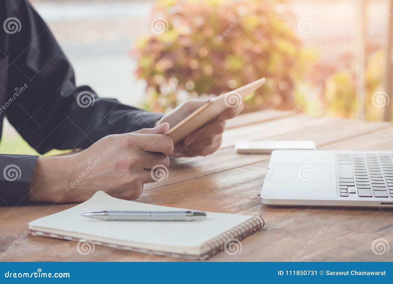 Hombre de negocios usando la tableta que trabaja con el ordenador portátil y el teléfono celular