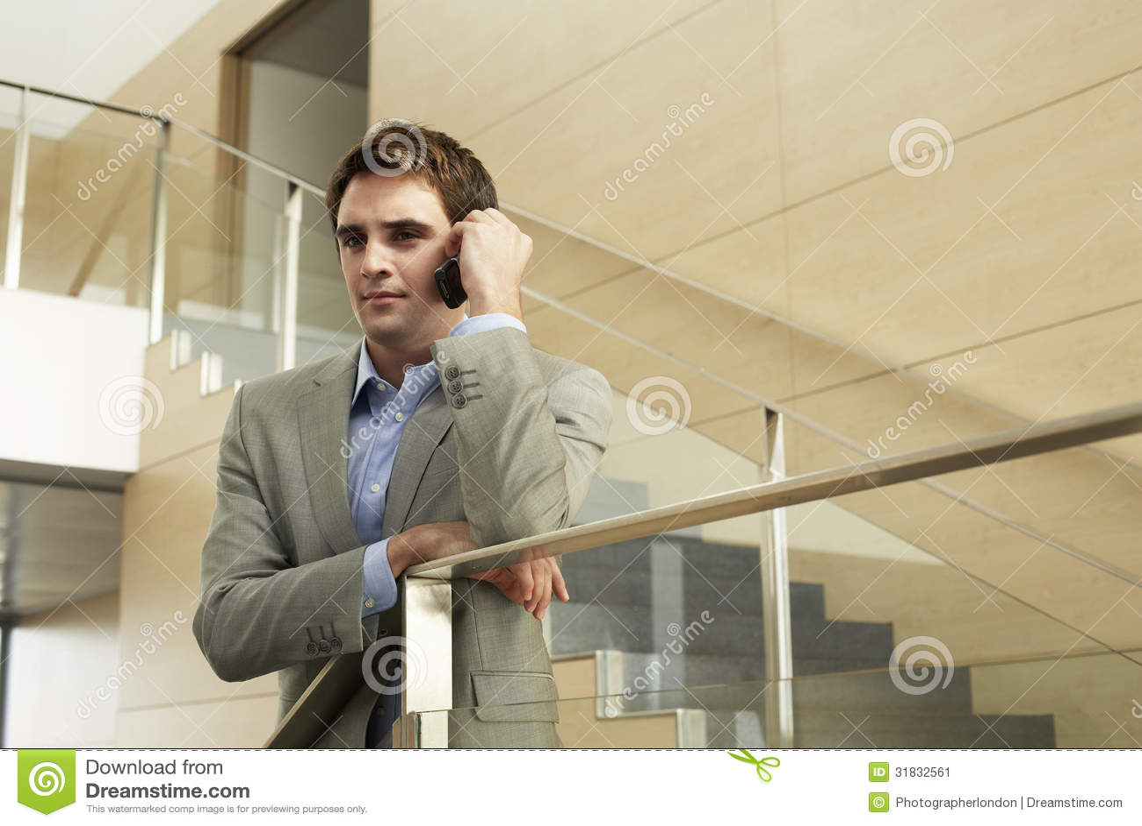 Hombre de negocios Using Cellphone While que se inclina en la verja de cristal