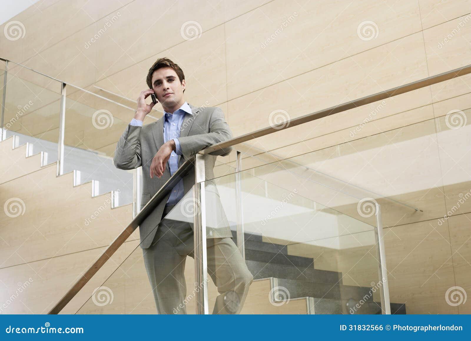 Hombre de negocios Using Cellphone While que se opone a la verja de cristal