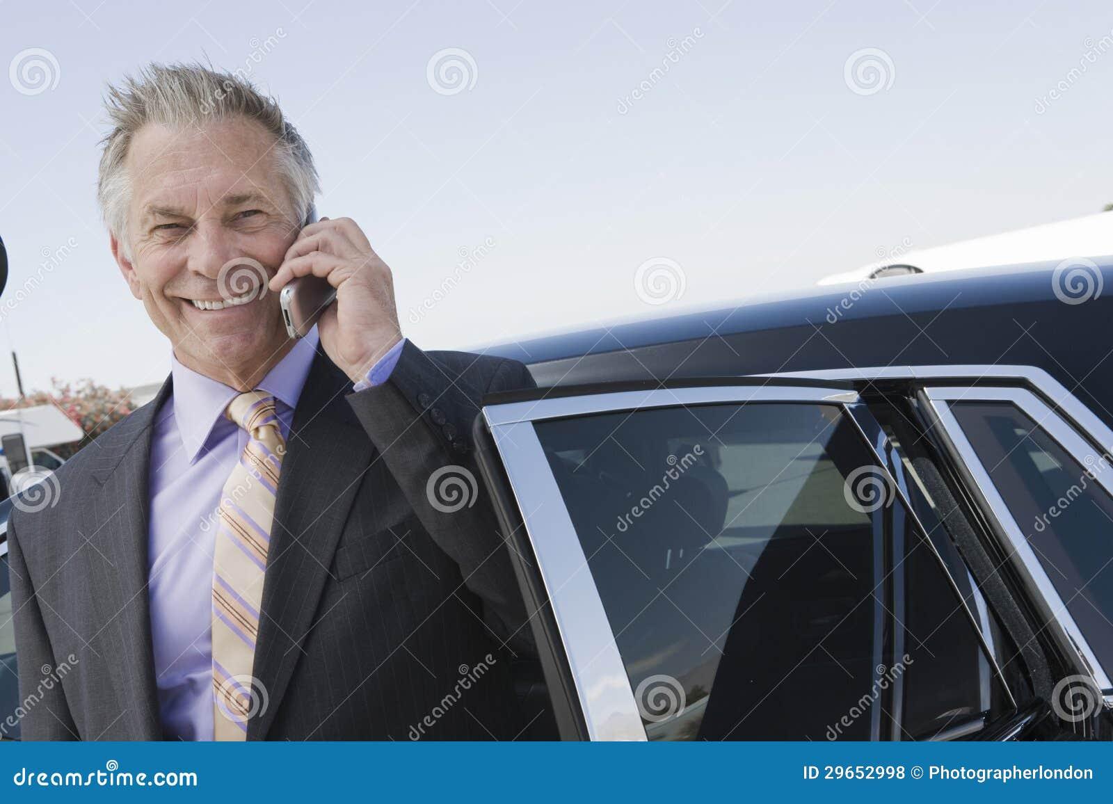 Hombre de negocios Using Cellphone Standing en coche