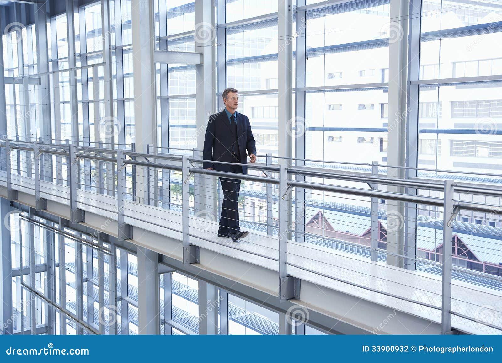 Hombre de negocios Walking By Railing en oficina moderna
