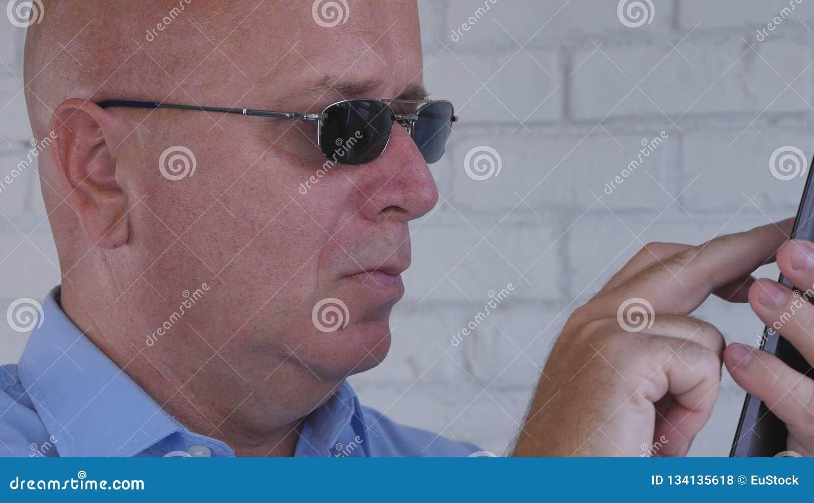 Hombre de negocios Wearing Sunglasses Text usando la comunicación de Smartphone