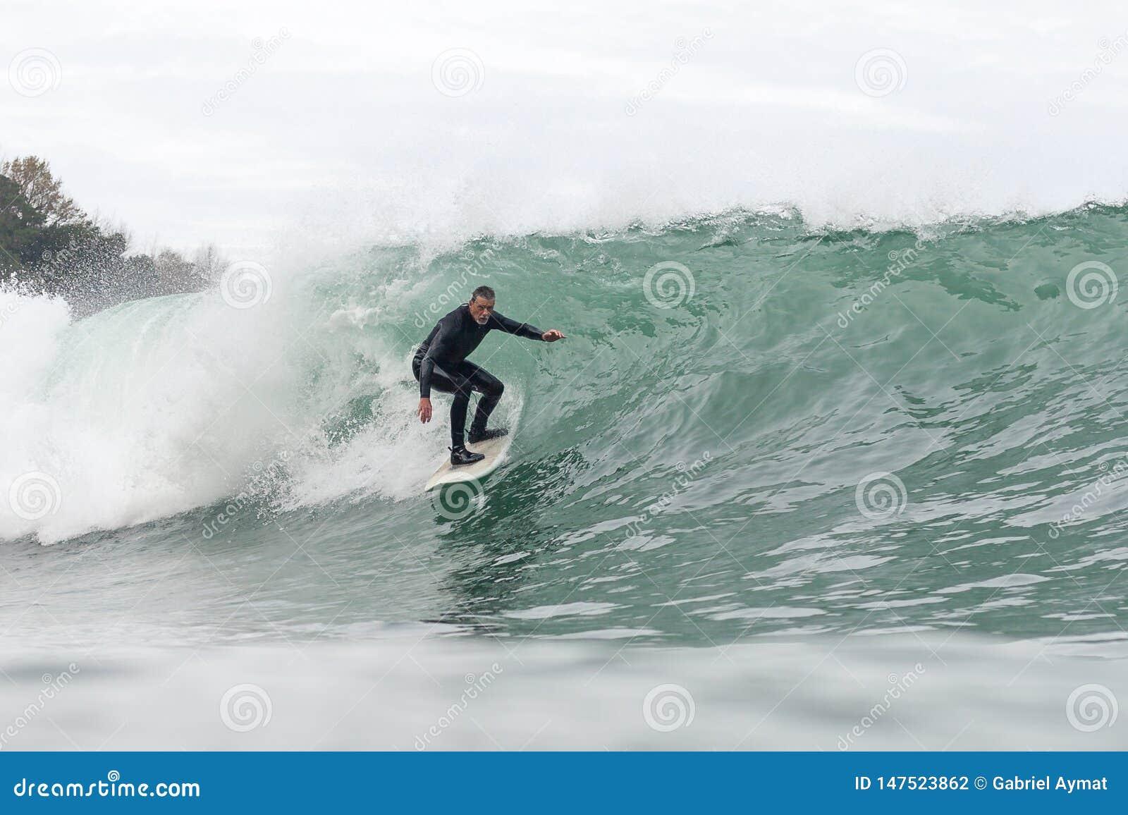 Hombre de 68 a?os que practica surf una onda grande