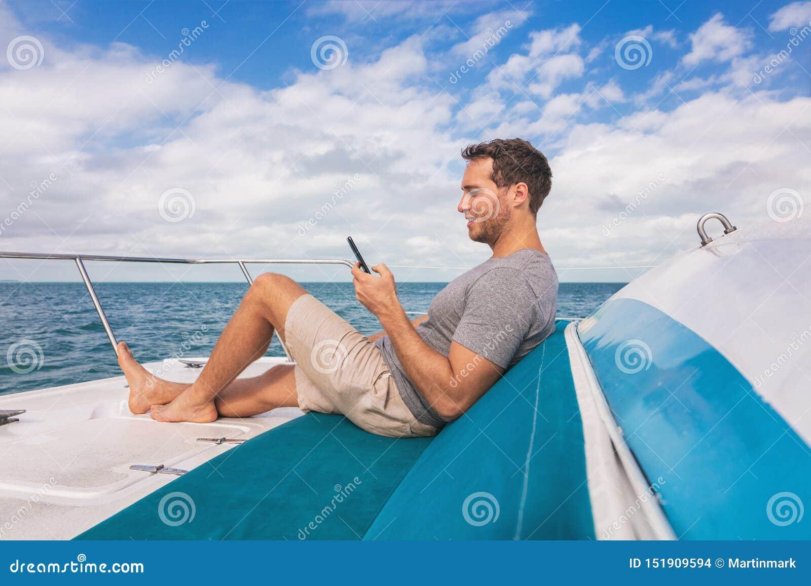 Hombre del barco usando el teléfono móvil que manda un SMS en Internet por satélite mientras que se relaja en la cubierta del luj