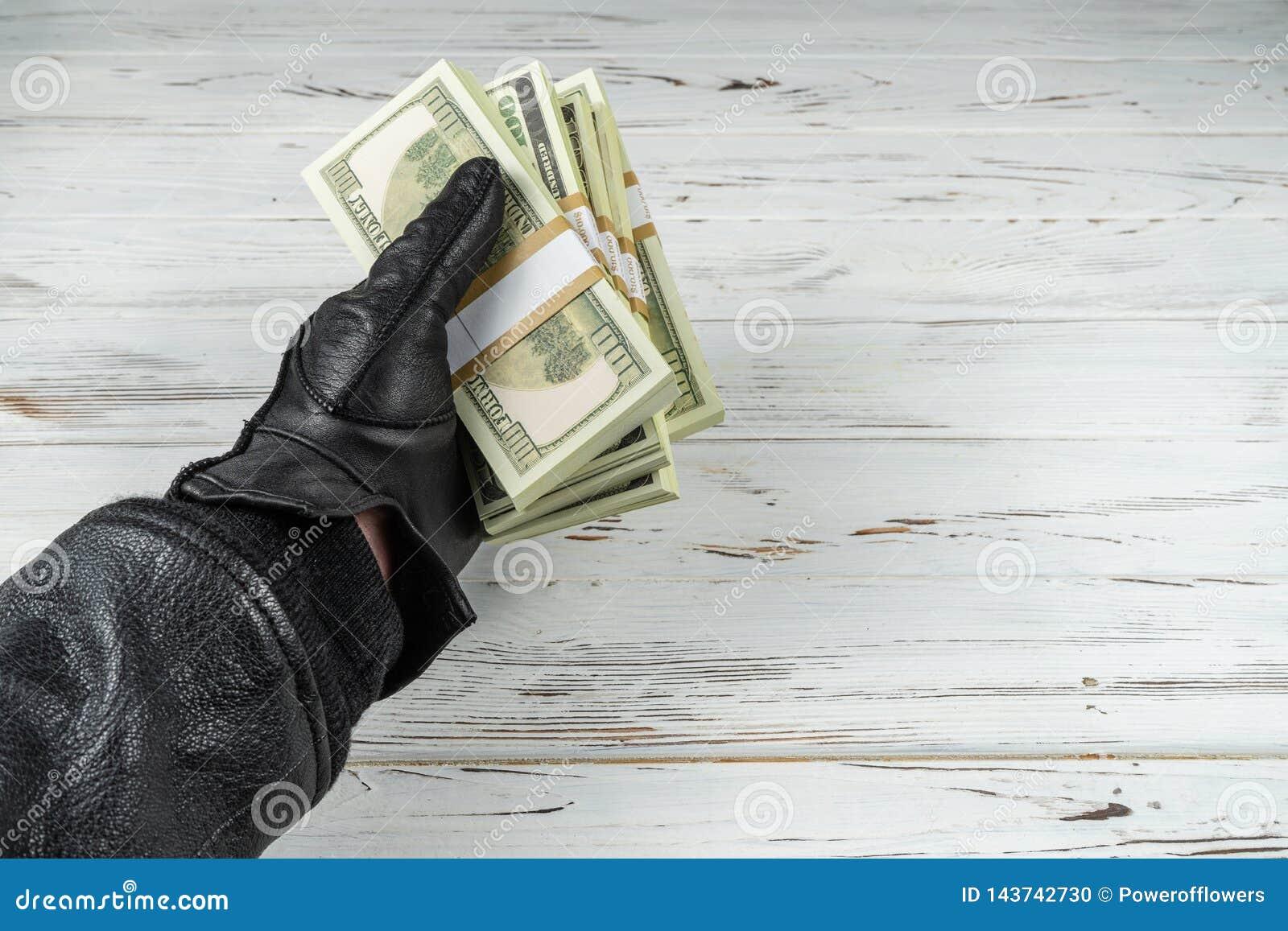 Hombre del concepto del crimen en los guantes de cuero negros que sostienen ladrillos del dinero