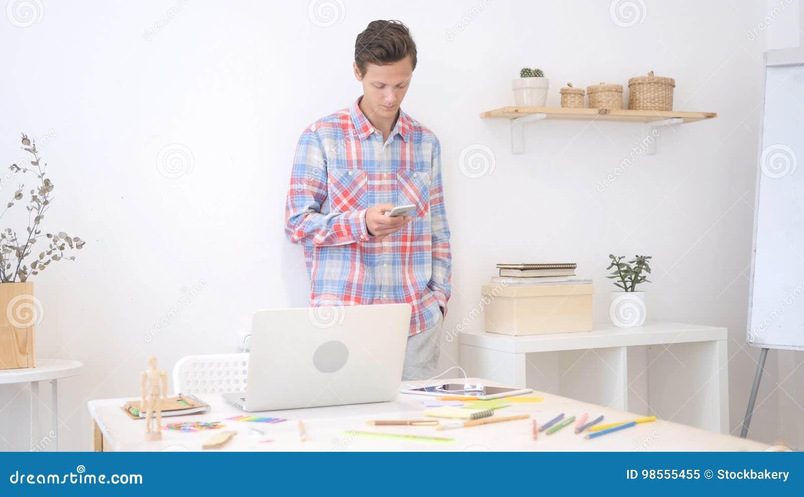 Hombre del diseñador que usa smartphone en la oficina del creatve que envía el mensaje en medios sociales