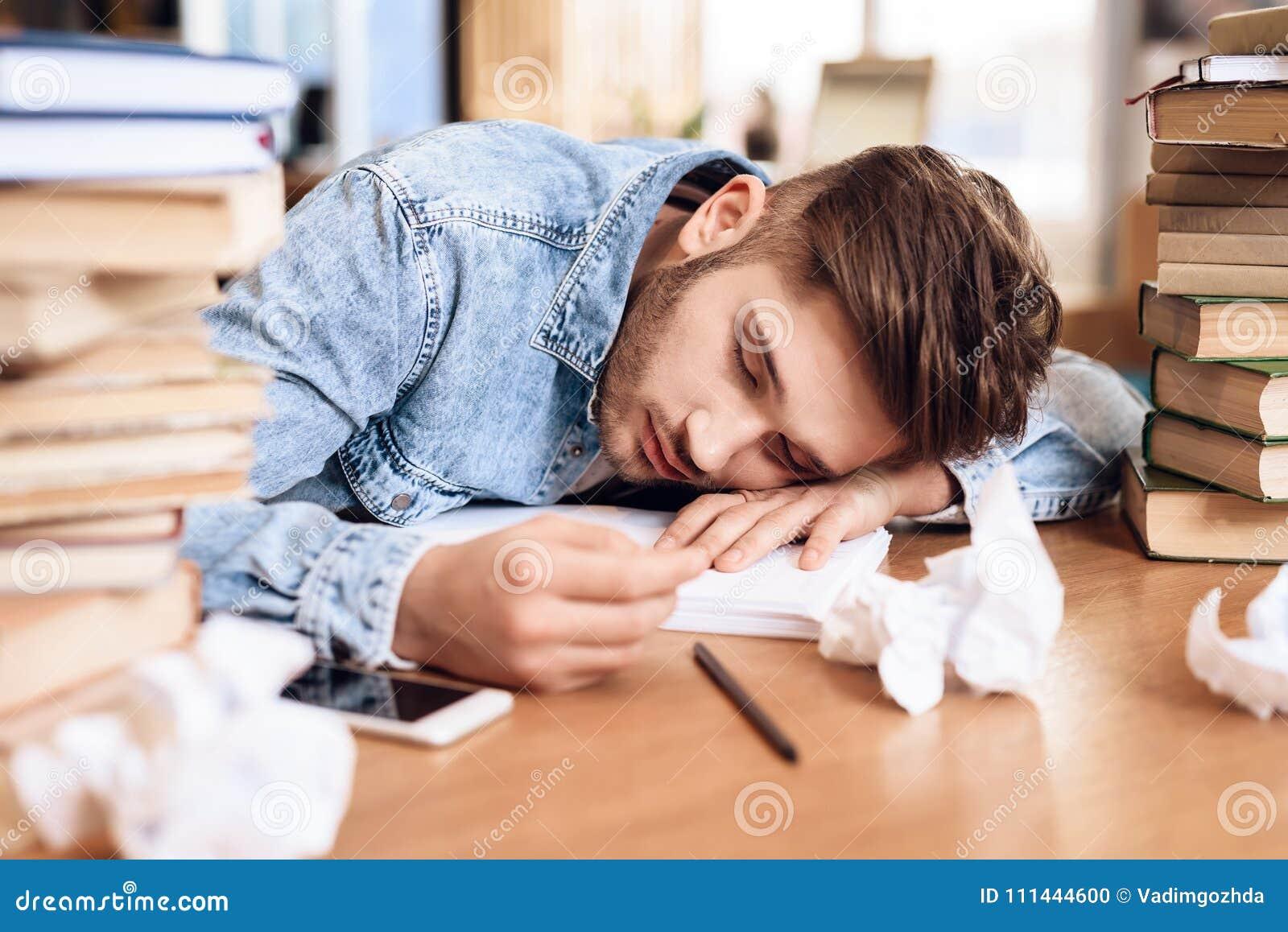 Hombre rodeado por Freelancer libros que duerme el los en del escritorio rFwqr