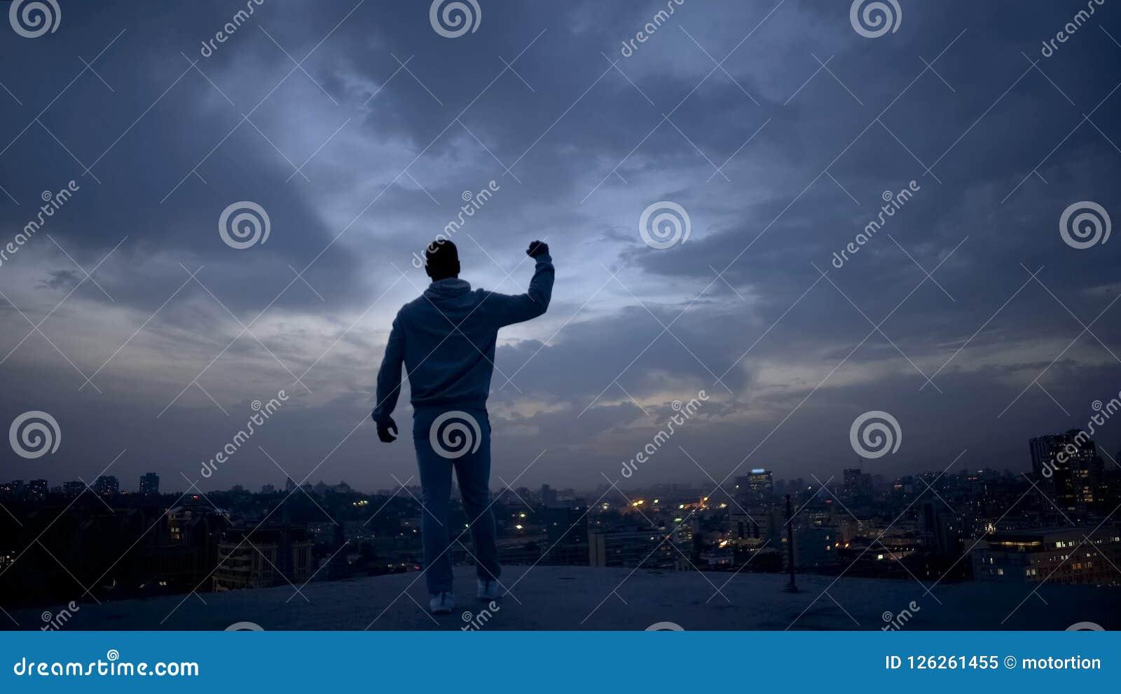 Hombre del ganador que disfruta de éxito en el fondo del paisaje urbano de la noche, dirección personal