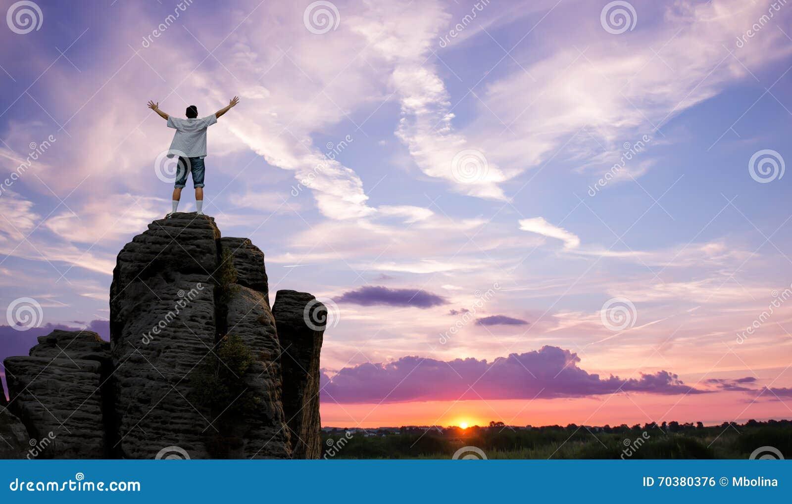 Hombre del ganador que se coloca en el top de la opinión panorámica de la montaña