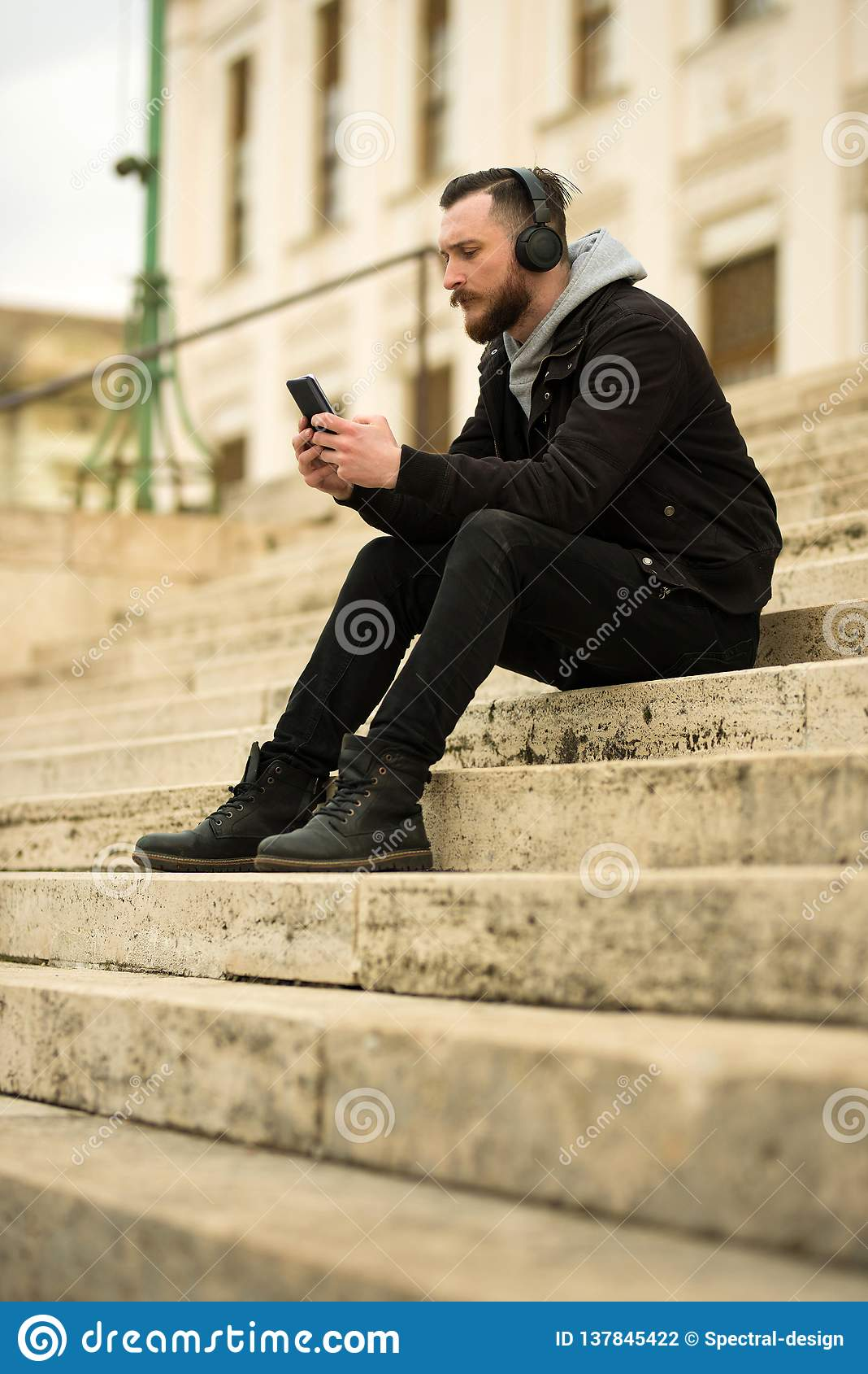 Hombre del inconformista en las escaleras con un smartphone