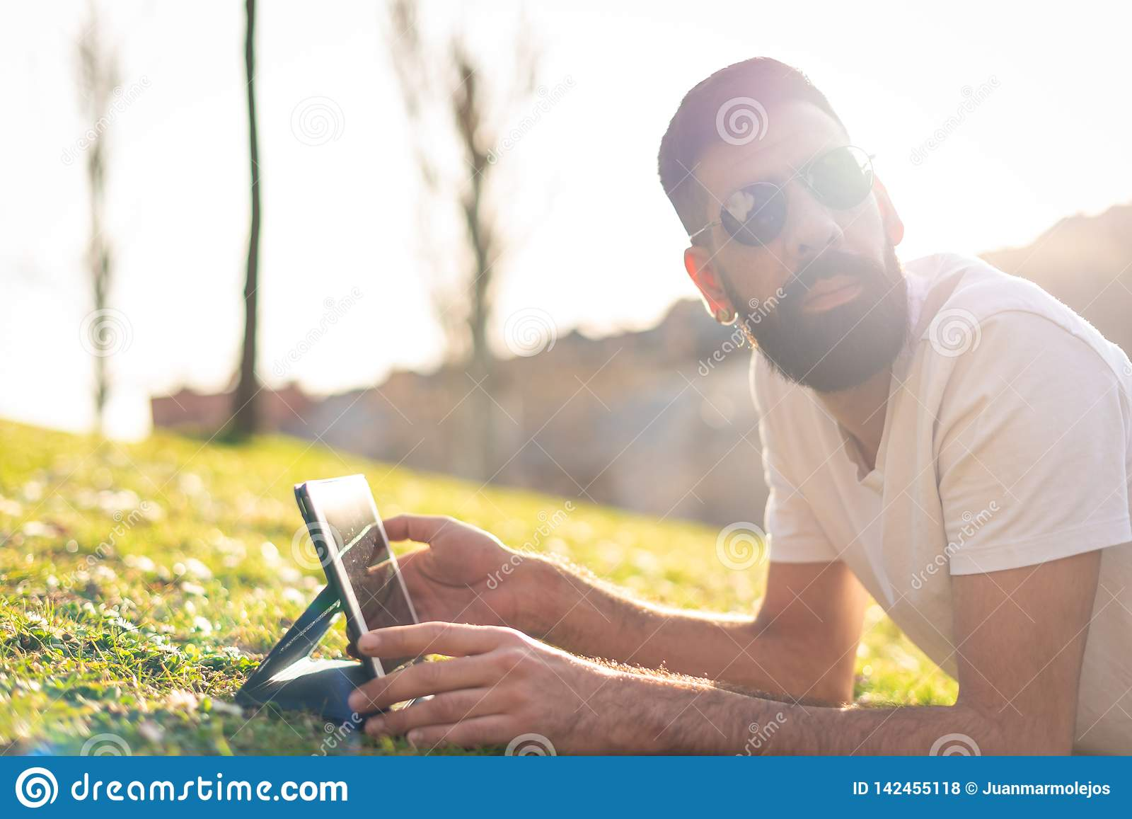 Hombre del inconformista usando una tableta digital en un parque