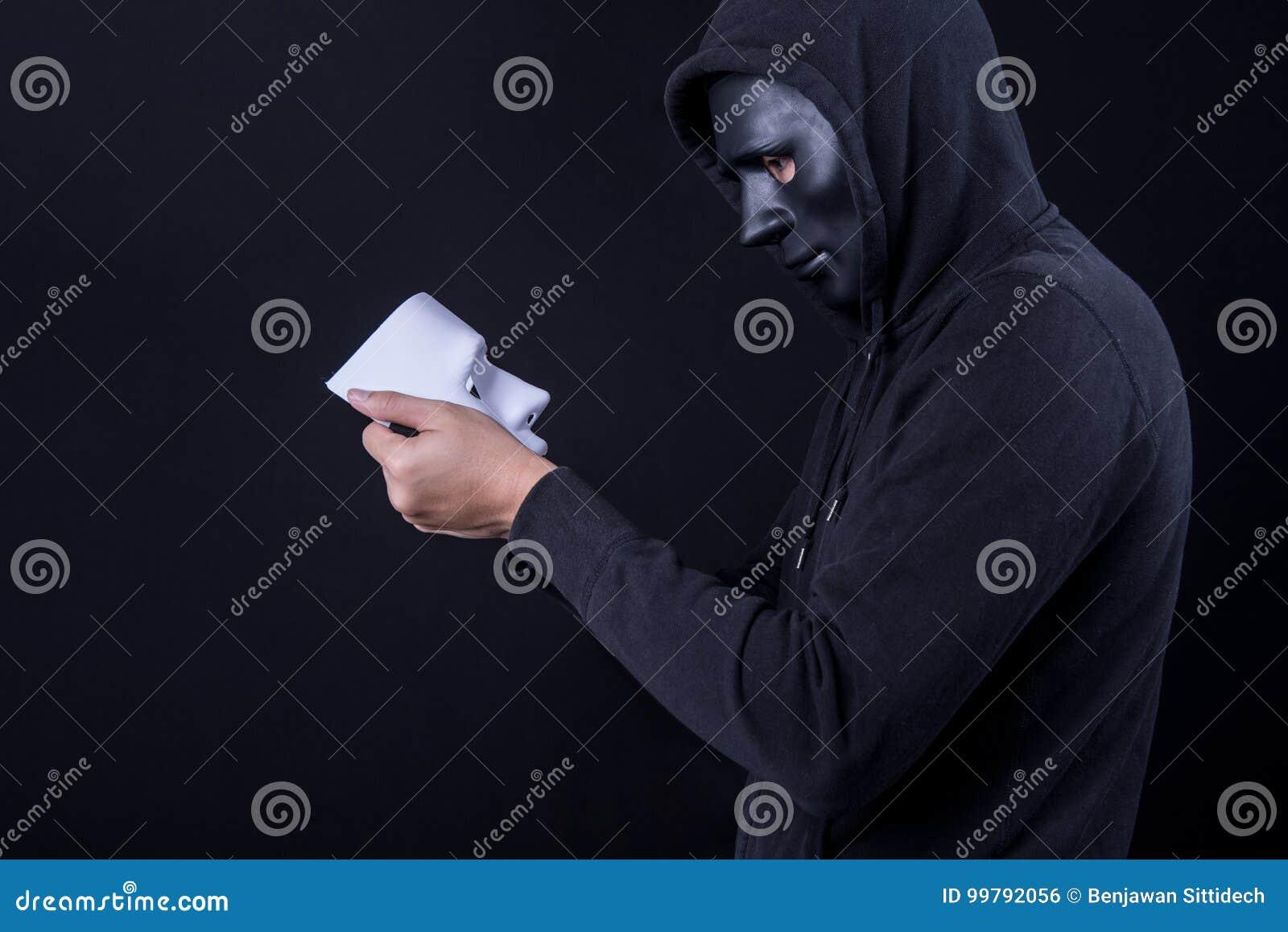 Hombre del misterio que lleva a cabo y que mira la máscara blanca