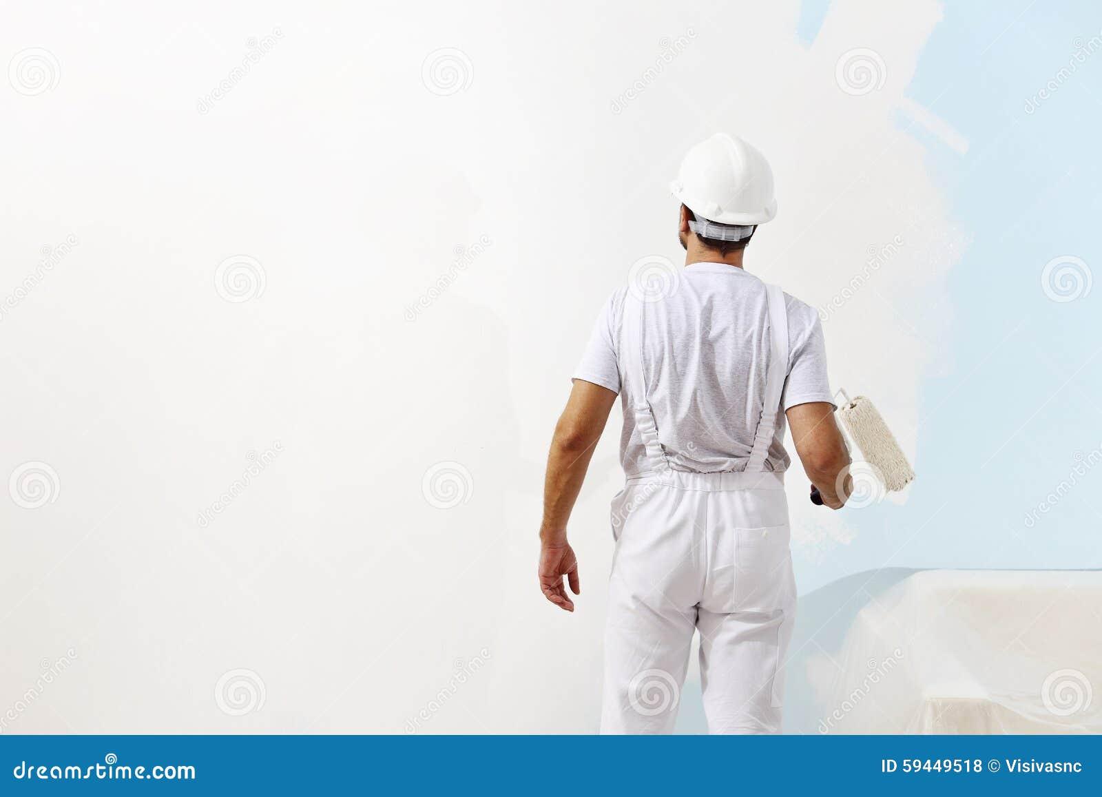 Hombre del pintor en el trabajo con un rodillo de pintura, pintura de pared