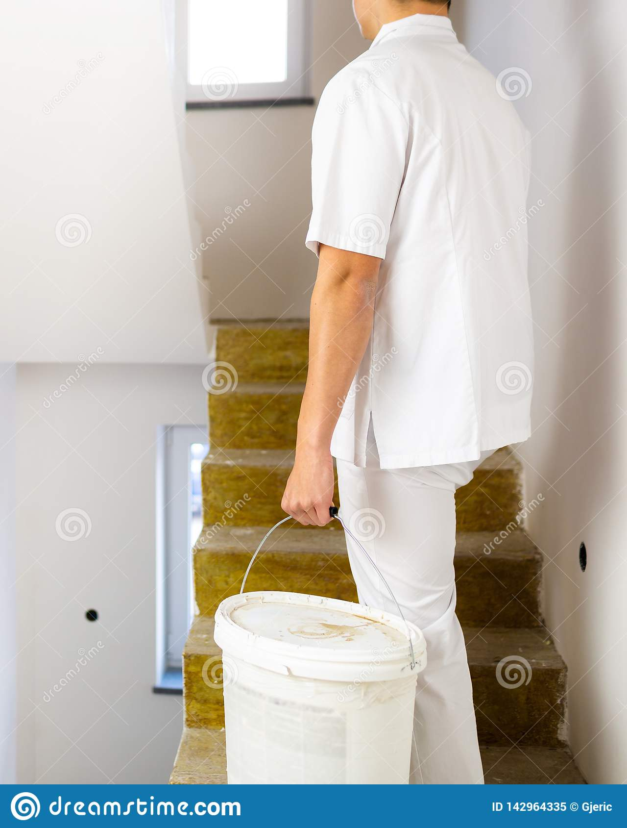 Hombre del pintor que trabaja en las paredes blancas de una pintura de casa