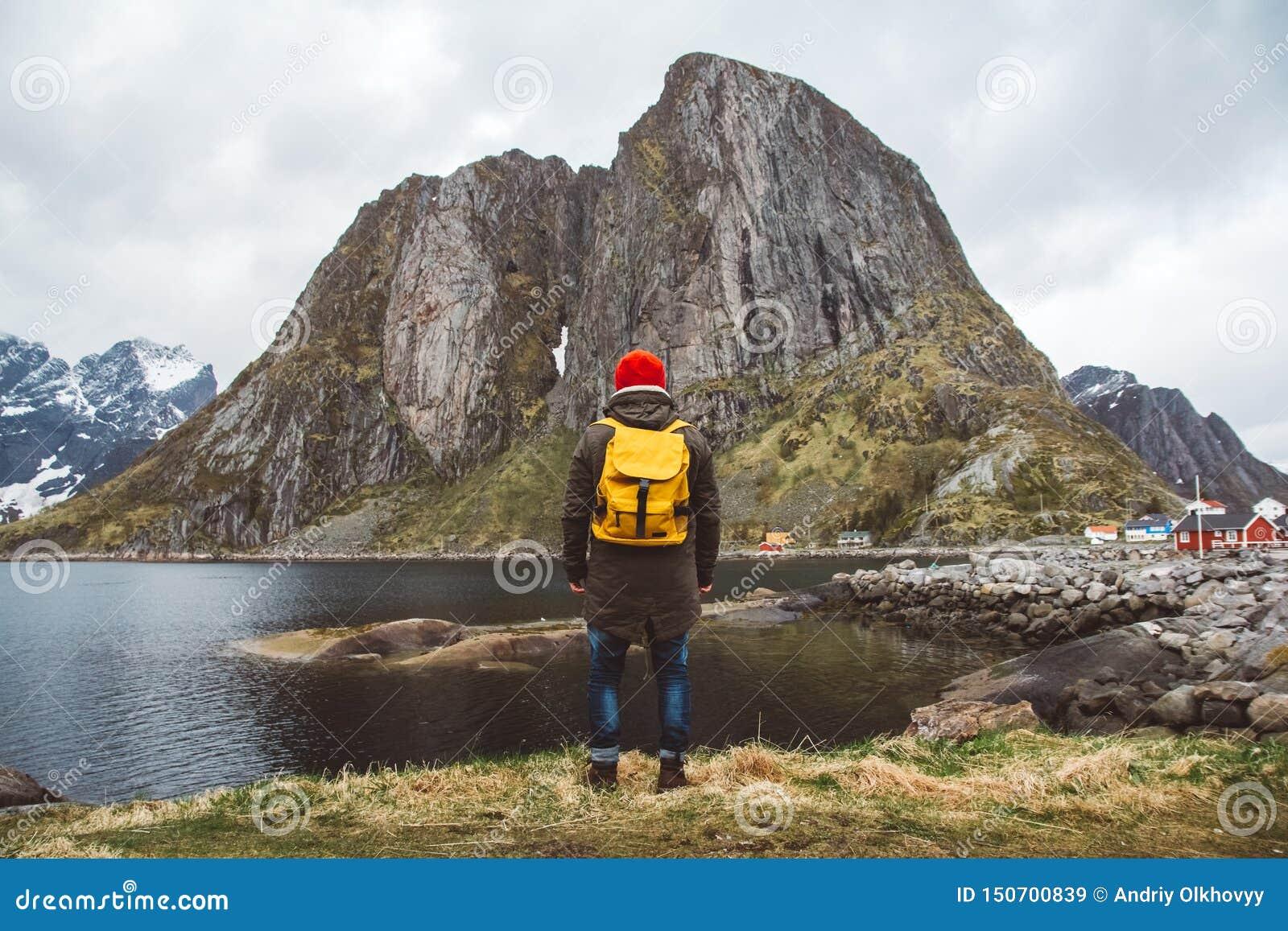 Hombre del viajero con una mochila amarilla que lleva una situación roja del sombrero en el fondo de la montaña y del lago Forma