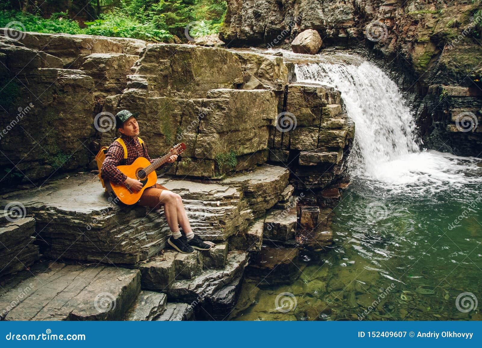 Hombre del viajero con una mochila que toca la guitarra contra una cascada Espacio para su mensaje de texto o contenido promocion