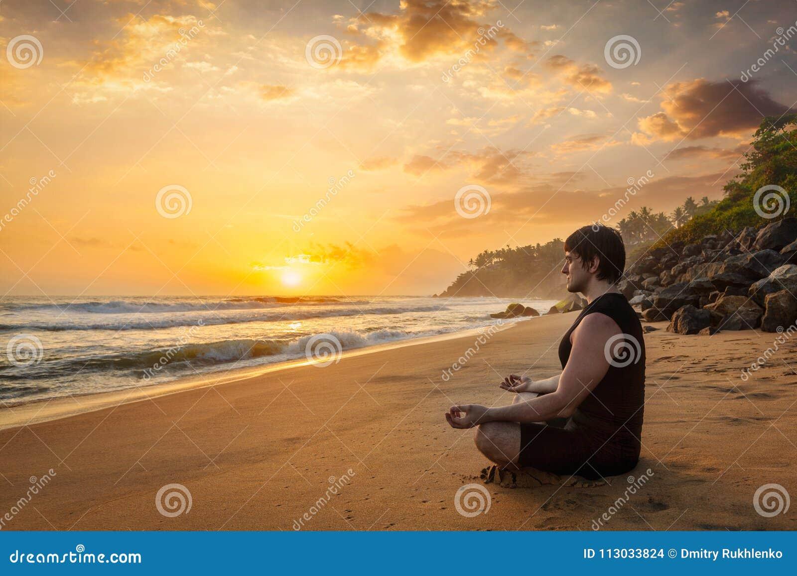 Hombre deportivo joven del ajuste que hace la yoga que reflexiona sobre la playa tropical