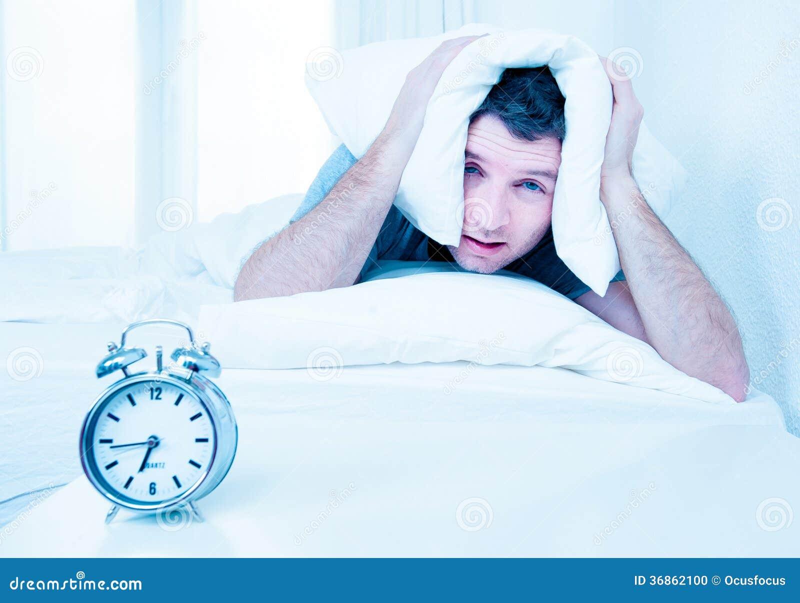 Hombre durmiente molestado por el mornin temprano del despertador