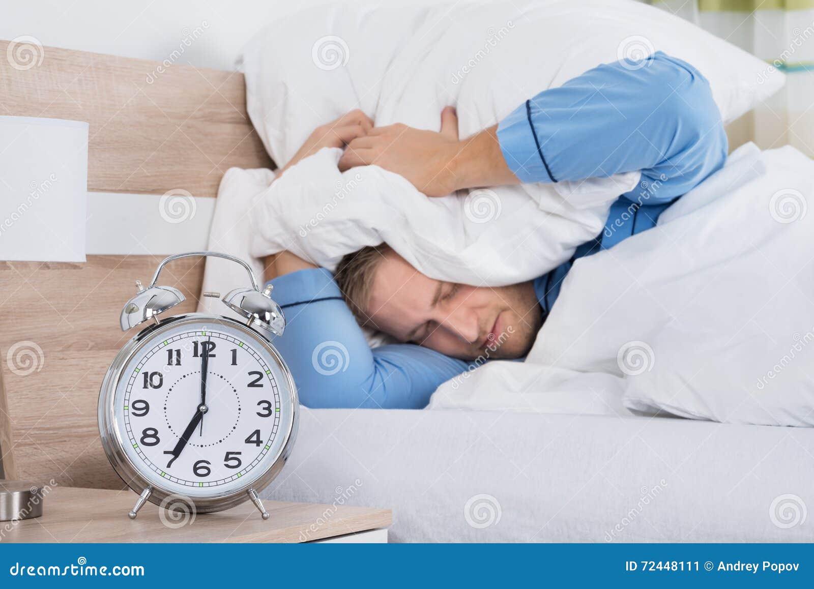 Hombre durmiente molestado sonando el despertador