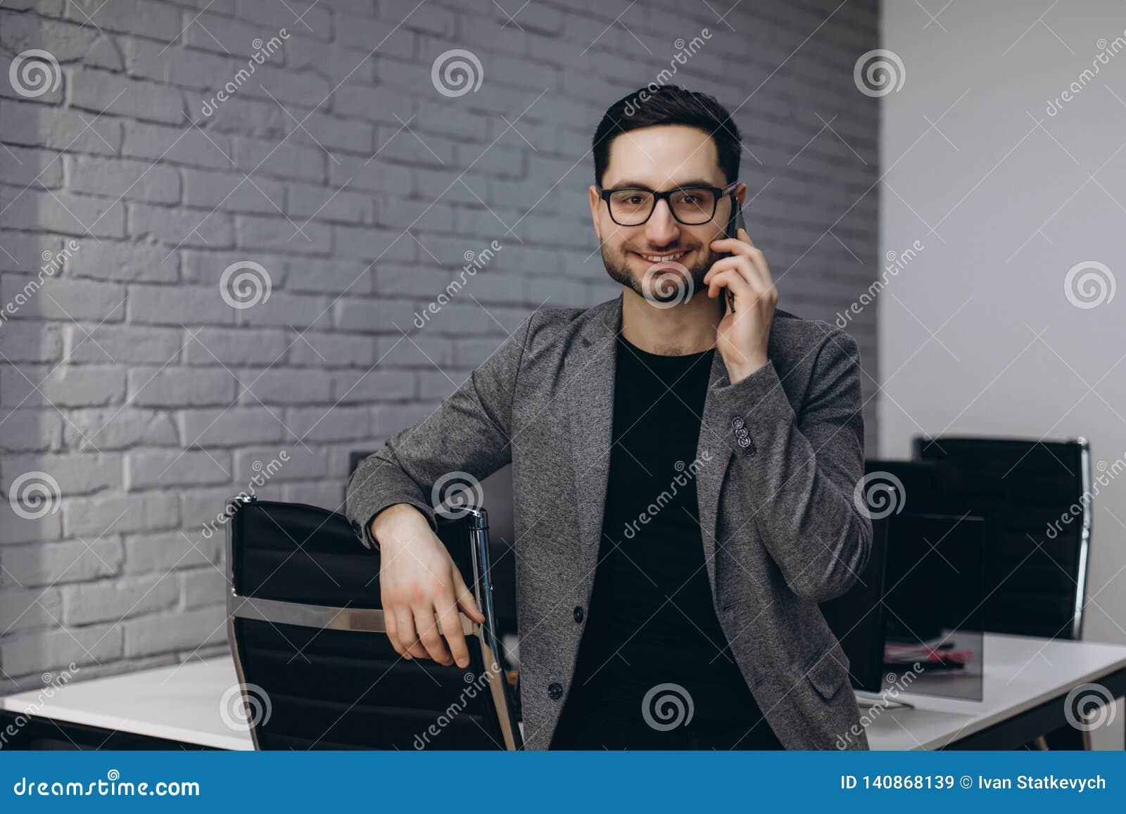 Hombre ejecutivo sonriente barbudo moreno joven hermoso atractivo del trabajador en el lugar de trabajo de la estación de trabajo