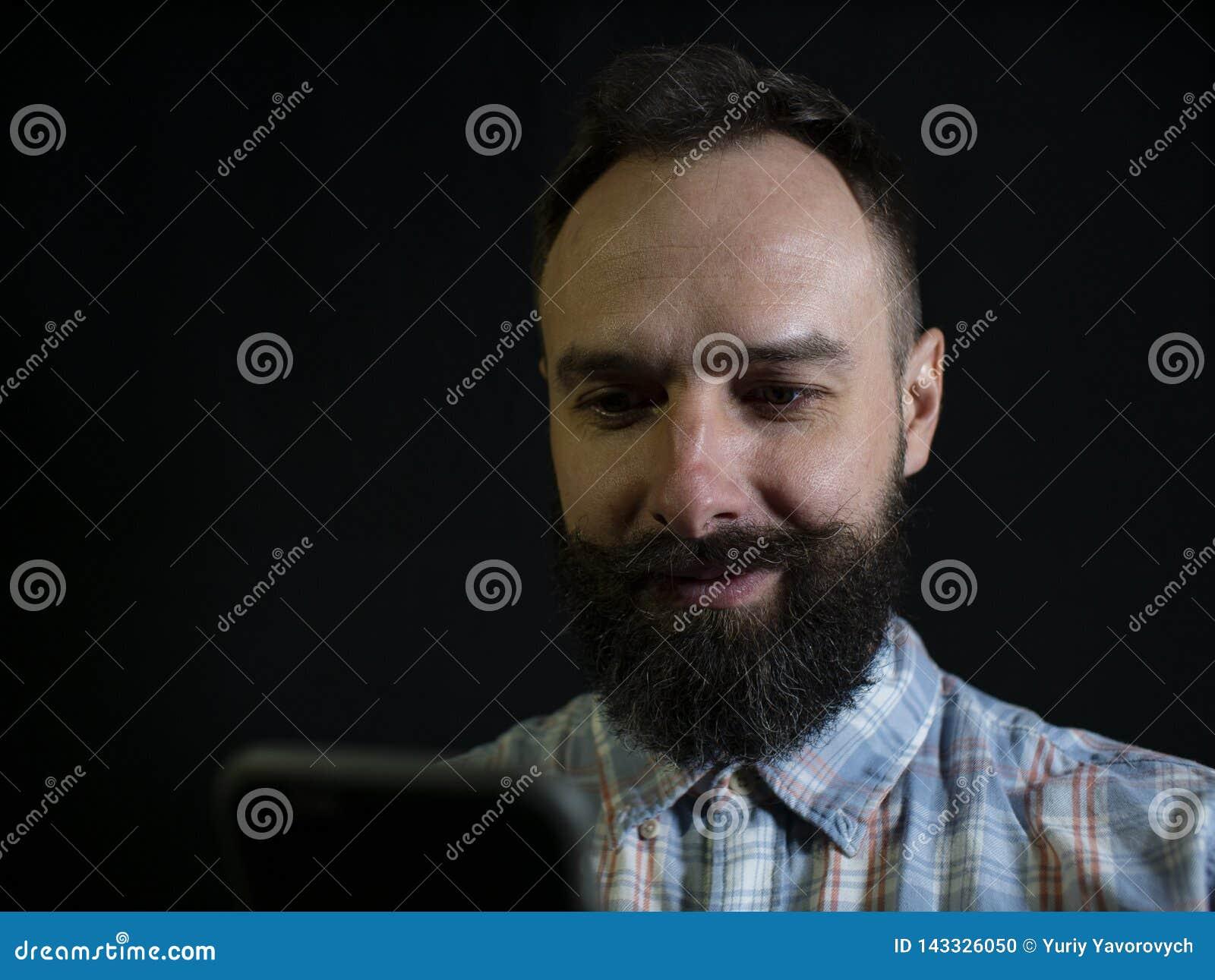 Hombre elegante con una mirada de la barba y del bigote en el teléfono y la sonrisa en un fondo negro
