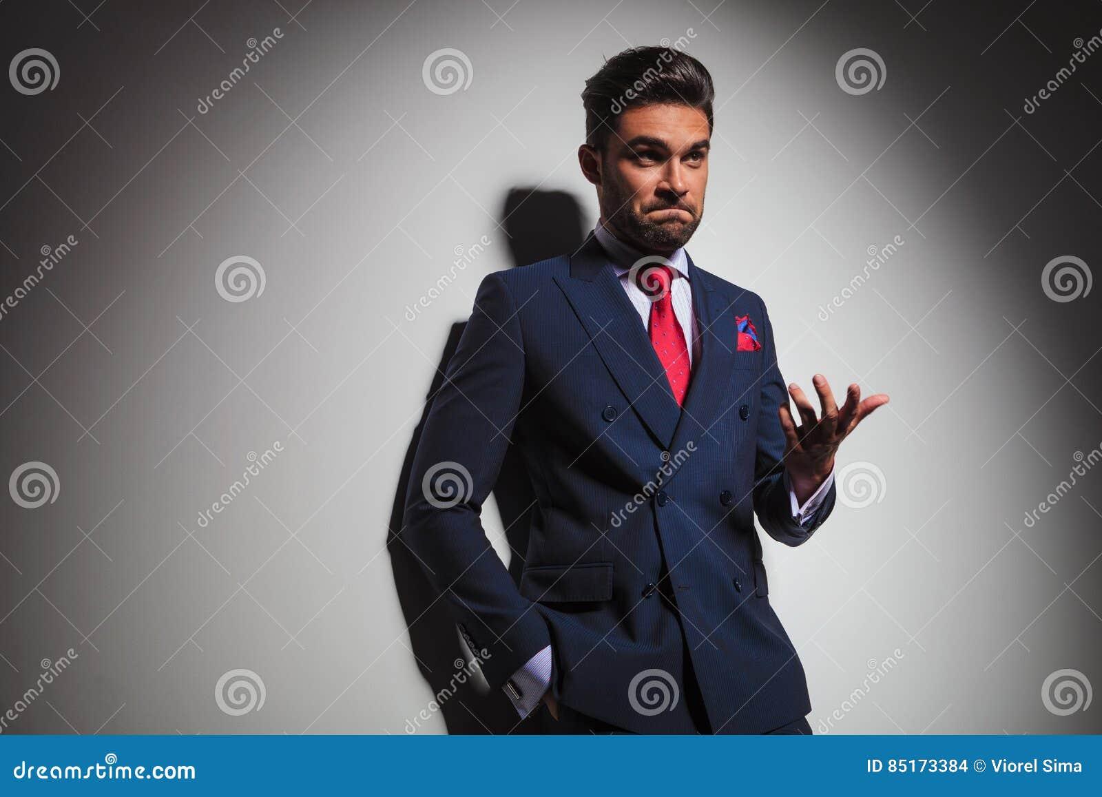Hombre elegante confuso que gesticula y que hace un fa estúpido indeciso