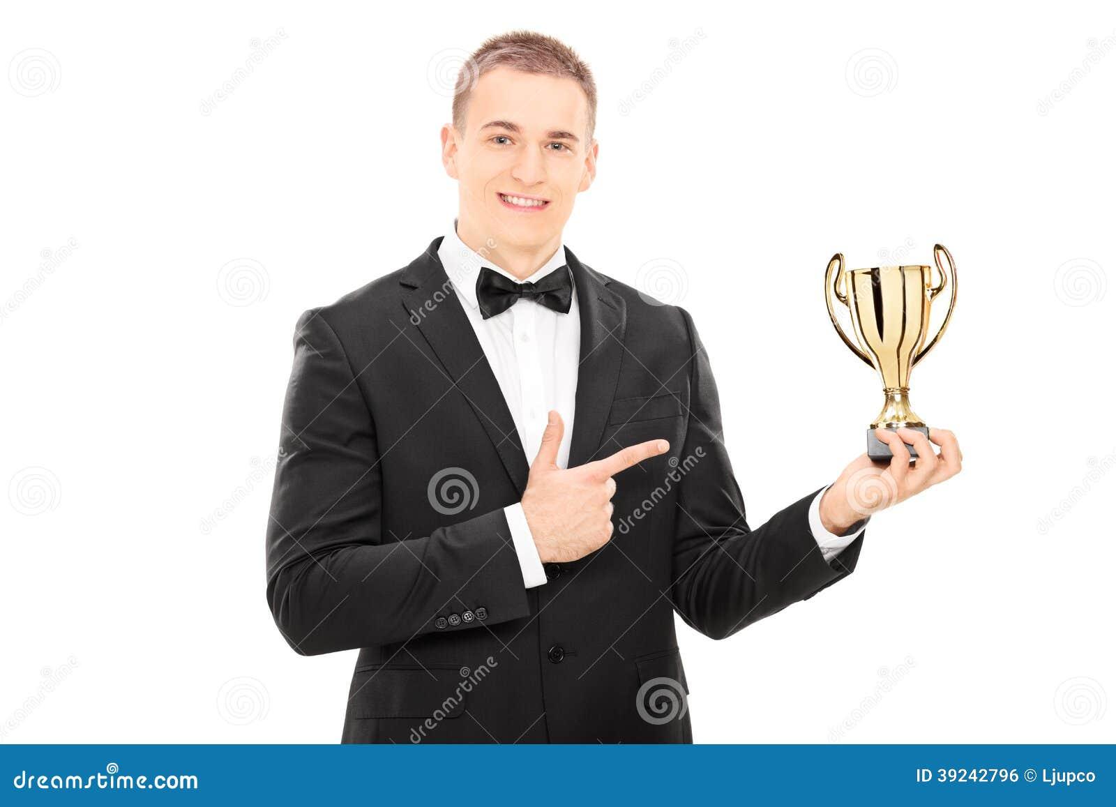 Hombre elegante que sostiene un trofeo
