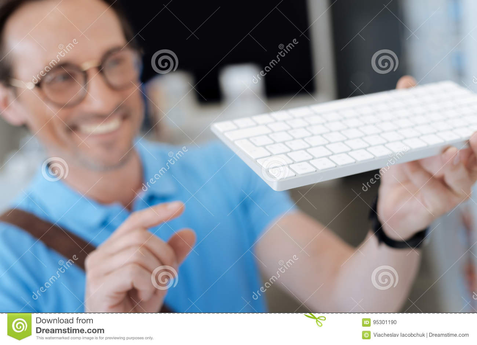 Hombre emocionado que mira el teclado para su ordenador en la sala de exposición