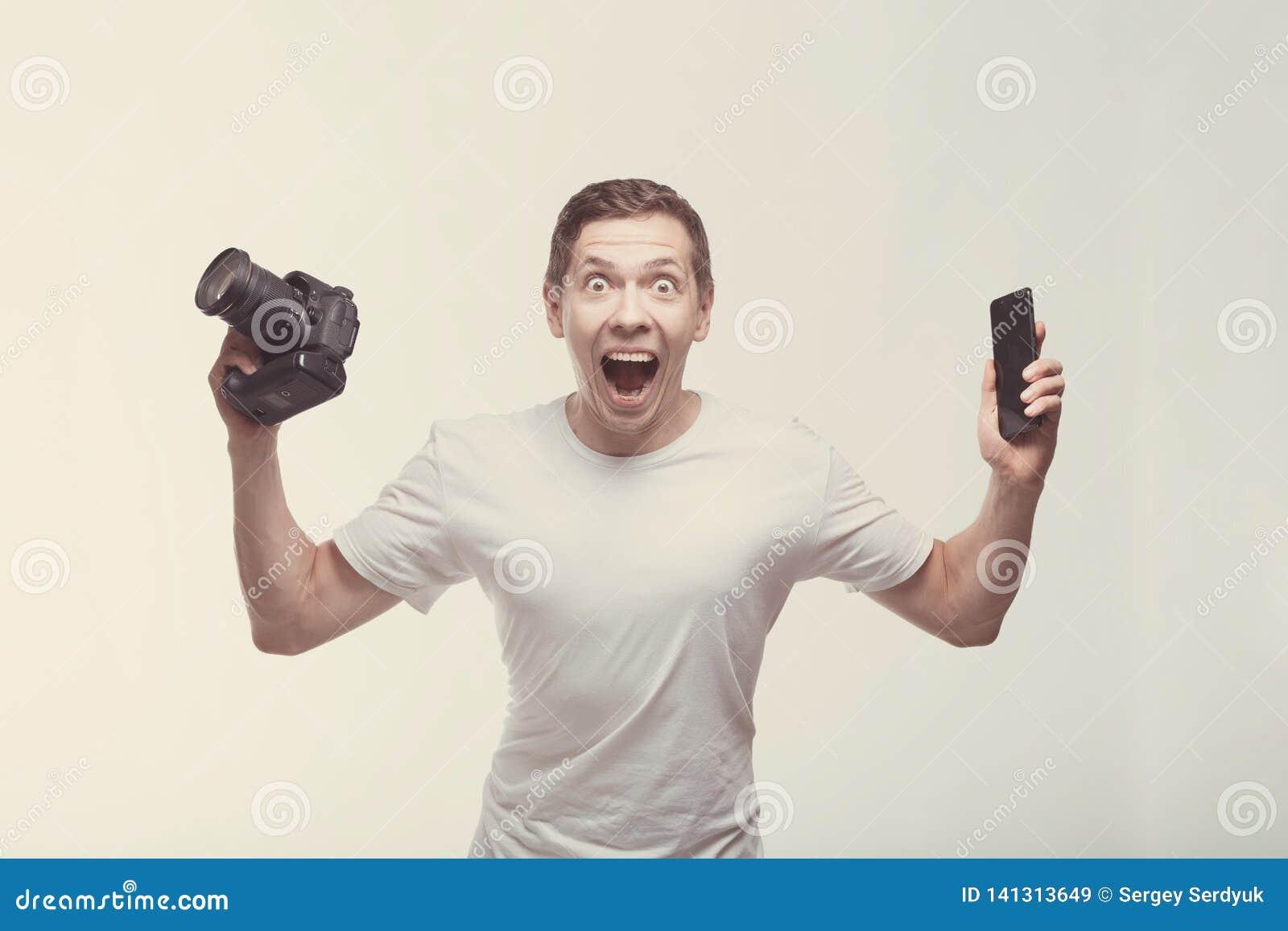 Hombre emocional con la cámara aislada en fondo ligero Cámara y smartphone de la tenencia del hombre joven con la victoria que gr