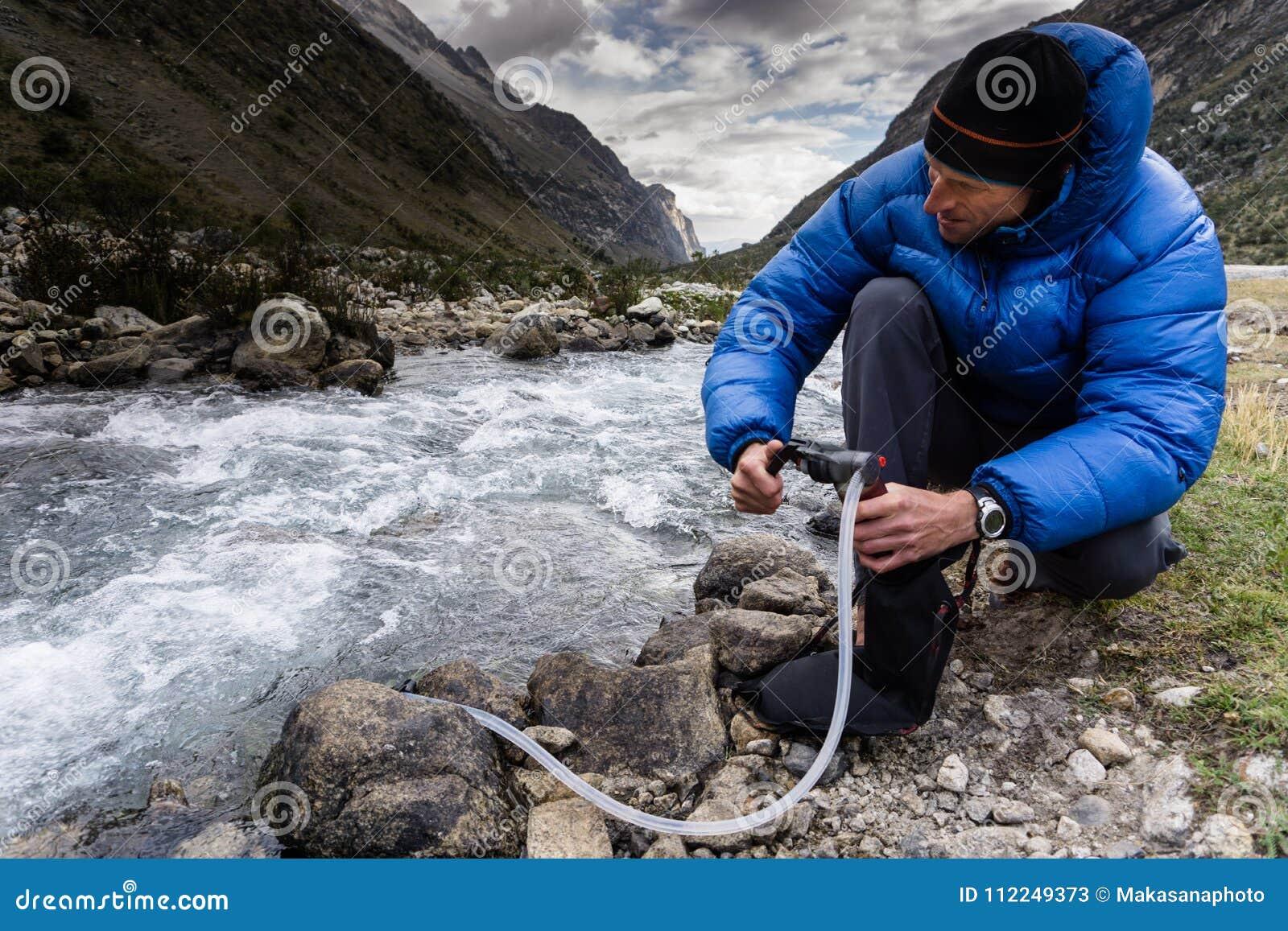 Hombre en agua potable de filtración abajo de la chaqueta azul de un río de la montaña en Perú