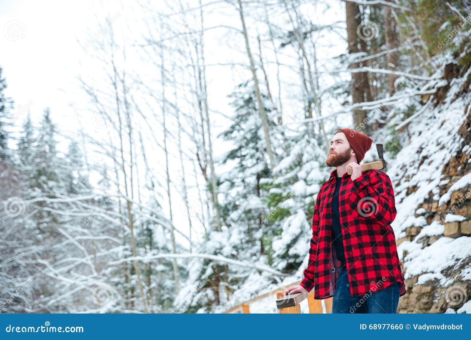 Hombre en camisa a cuadros con el hacha que se coloca en el bosque del invierno