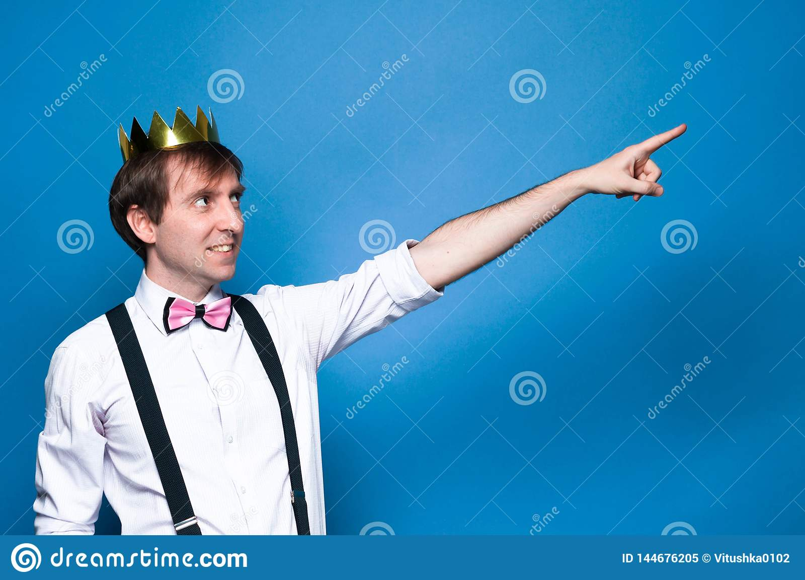 Hombre en camisa, liga, corbata de lazo y corona de oro, sonriendo, mirando lejos y ponting con el finger en distancia en fondo a