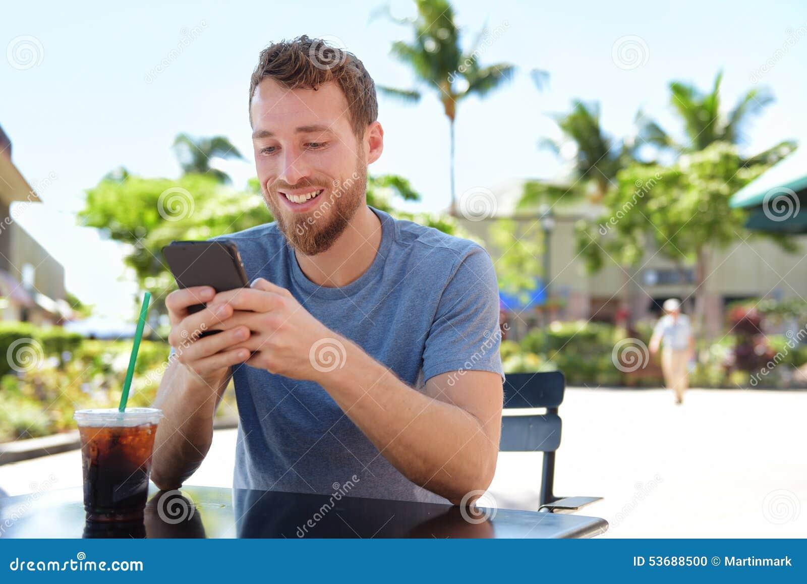 Hombre en el café usando envío de mensajes de texto elegante del app del teléfono