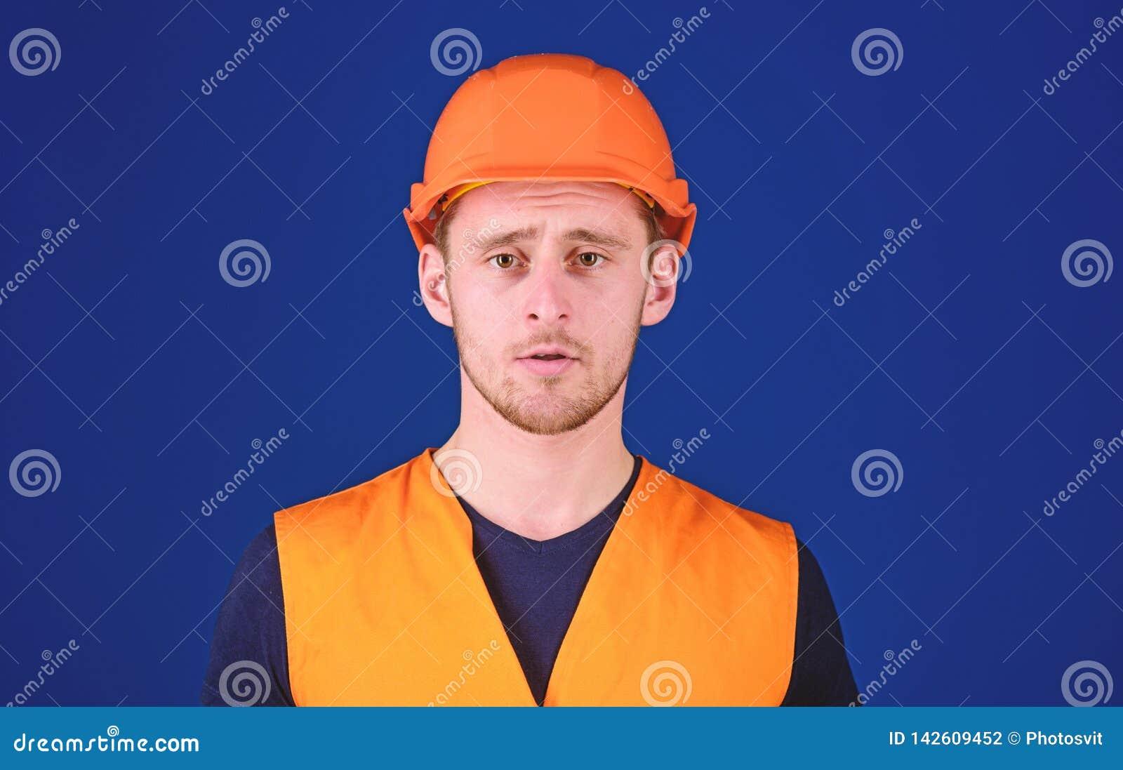 Hombre en el casco protector, el casco y el uniforme de trabajo, fondo azul Trabajador, contratista, constructor en cara tranquil