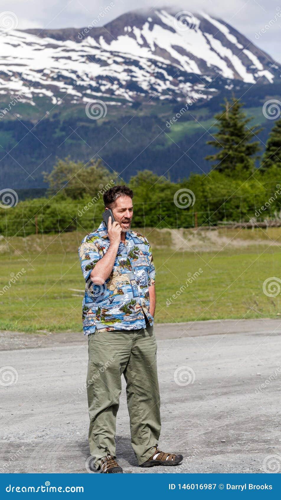 Hombre en el teléfono celular en desierto de Alaska
