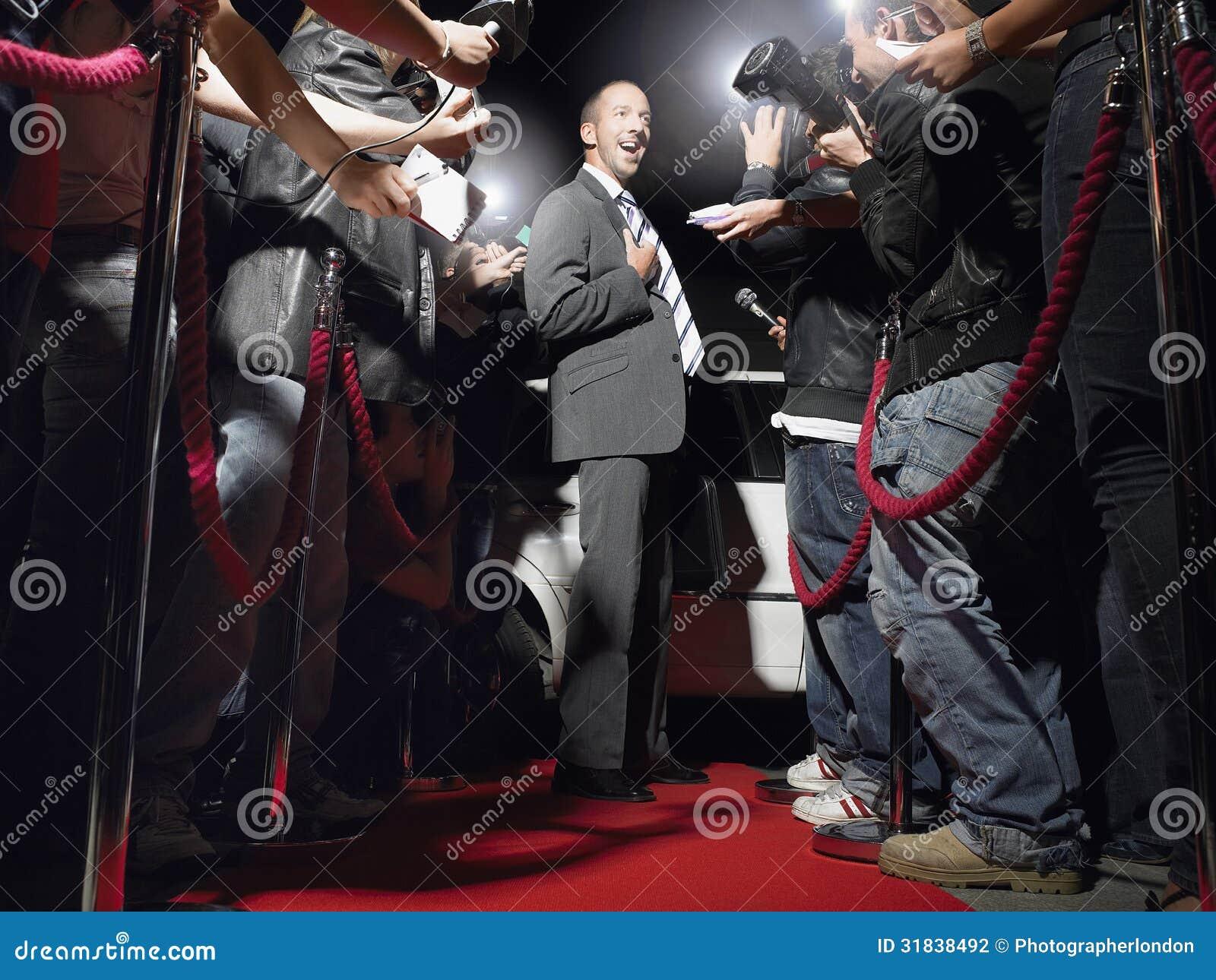 Hombre en la alfombra roja que presenta en Front Of Paparazzi