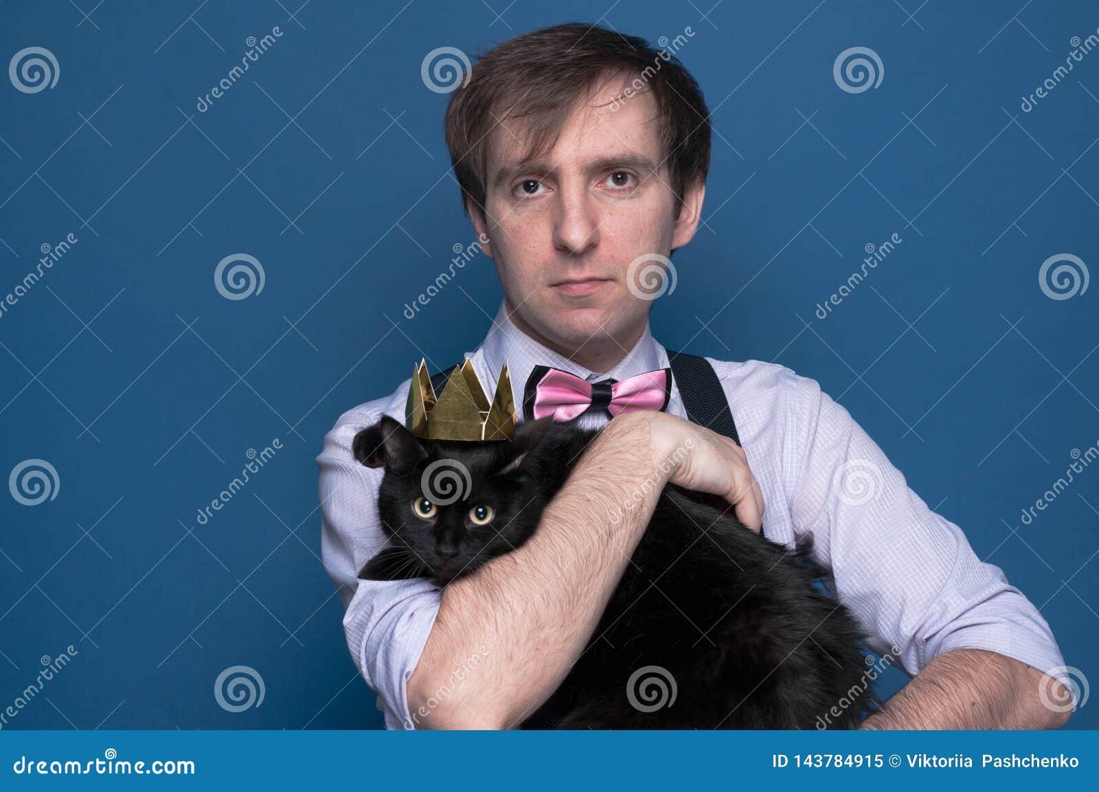 Hombre en la camisa, la liga rosada y la corbata de lazo sosteniendo el gato negro lindo en corona de oro brillante