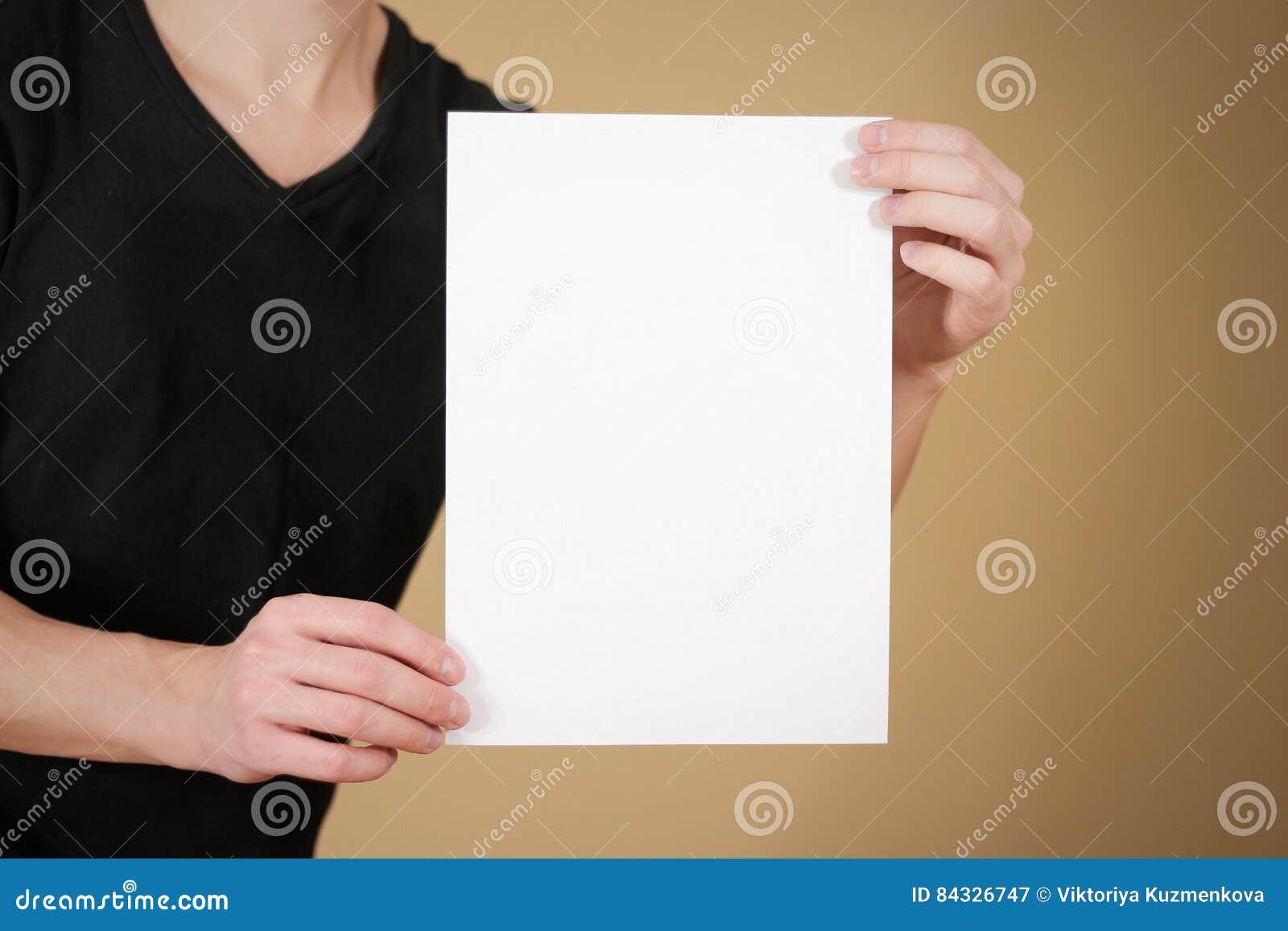 Hombre en la camiseta negra que sostiene el papel en blanco del blanco A4 Prospecto prese