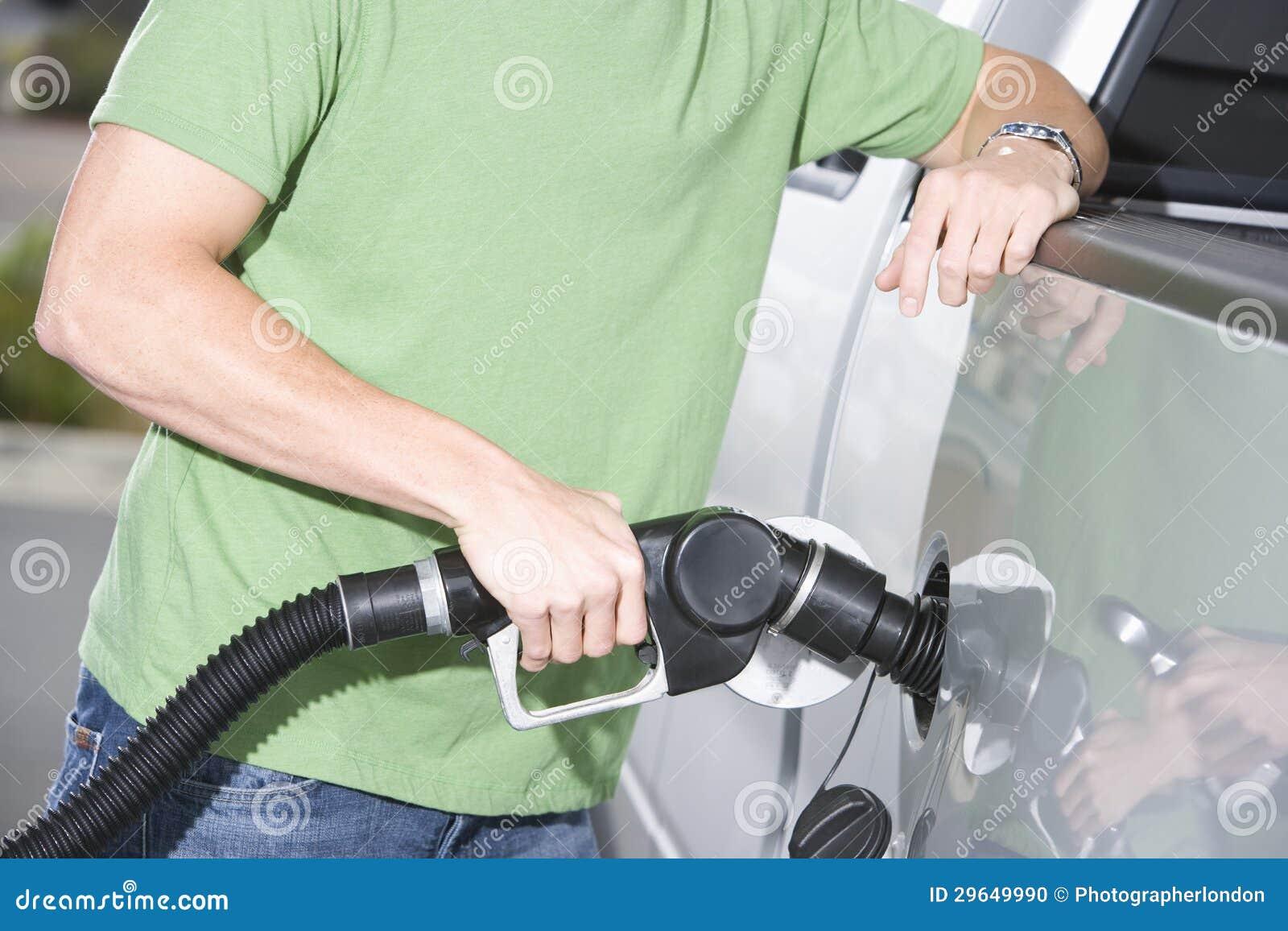 Hombre en la camiseta verde que reaprovisiona su coche de combustible