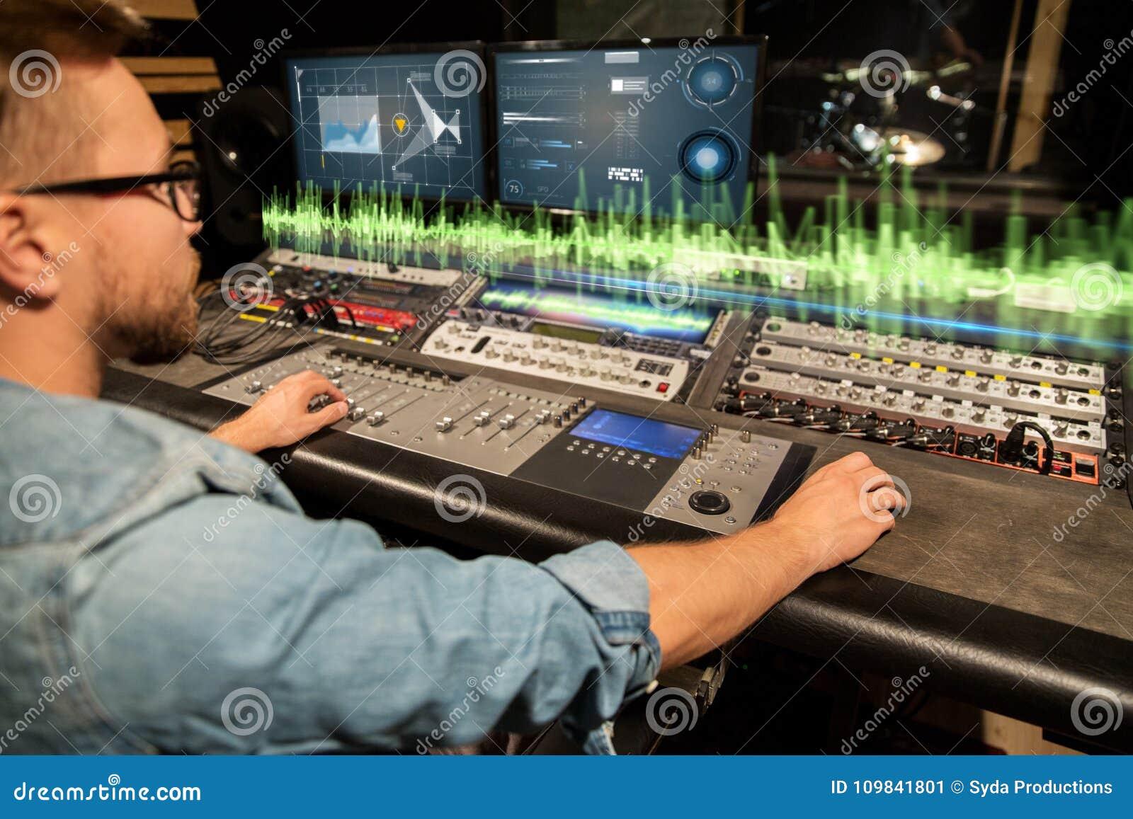 Hombre en la consola de mezcla en el estudio de grabación de la música