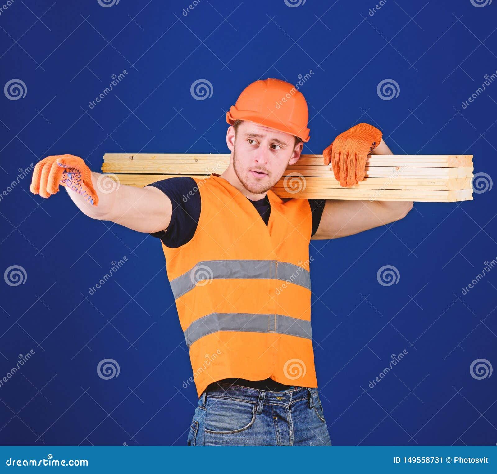 Hombre en la direcci?n punteaguda del casco, del casco y de los guantes protectores, fondo azul Carpintero, carpintero, construct