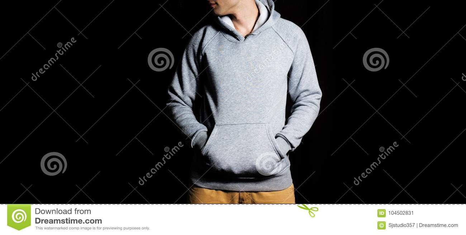 Hombre en la sudadera con capucha gris en blanco, camiseta en un fondo negro, mofa para arriba, espacio libre