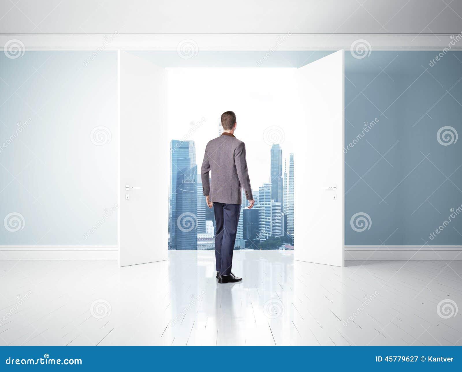 Hombre en las puertas abiertas que miran la ciudad