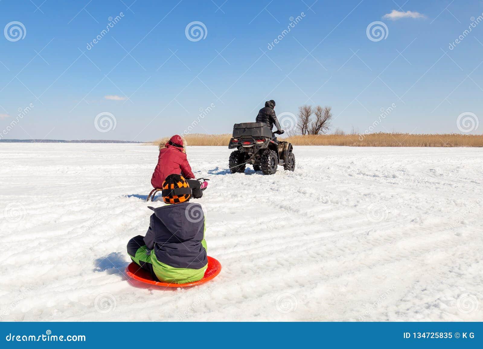 Hombre en los trineos que montan del quadbike de ATV con los niños a remolque en superficie congelada del lago en el invierno Dep
